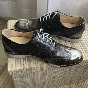 Cole Haan Metallic silver wing tip tie shoe.
